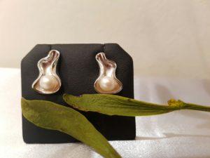 zilveren oorbel in vorm van een gekruld blad met een kleiner pareltje in.