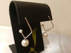 Zilveren oorbellen met parels, hoekig model, met rond pareltje los in hangend en klein pareltje op het uiteinde.