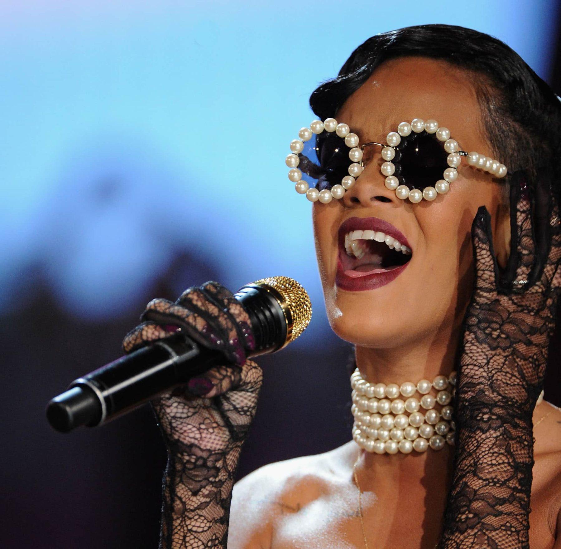 op de foto is een close-up te zien van Rihanna die een choker van vijf rijen parels draagt en een zonnebril bezet met parels. Ze houdt een micro vast en is aan het zingen.