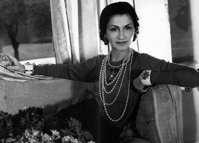 een wit-zwart foto van Coco Chanel waarop te zien is dat ze in de hoek van een zetel zit. Met vijf lange parelkettingen aan, in verschillende lengtes. Ook twee grote witte armbanden en ze kijkt zelfzeker in de camera.
