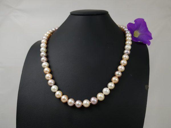 Halsketting van ronde parels in natuurlijke kleuren.
