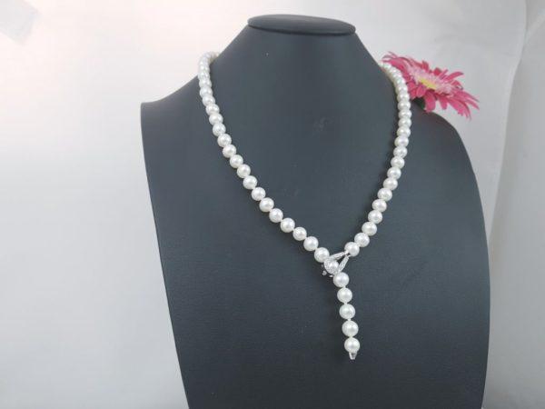 parelhalsketting met witgouden slot , waardoor dit een afhangend model wordt. Slot bezet met diamanten.