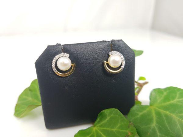 Gouden oorbellen met echte parels en diamanten.