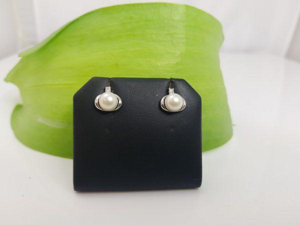 witgouden oorbellen op het oor
